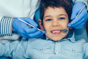 Boy dressed in blue getting dental treatment