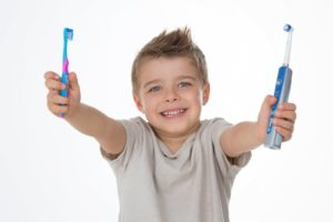 boy holding a manual toothbrush in his right hand and an electric toothbrush in his left hand