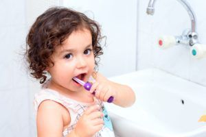 young female toddler with brown curly hair brushing her teeth next to a sink