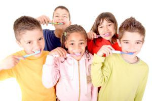 a group of kids brushing their teeth