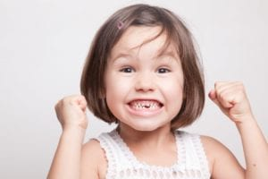 Little girl cheering with missing front tooth