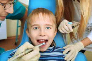 Little boy sitting in dental chair and receiving dental treatment